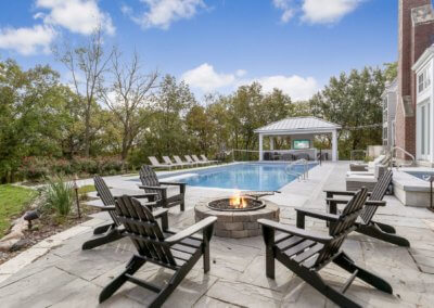 Backyard remodel featuring fire pit, in ground pool, hot tub, and covered entertainment space.