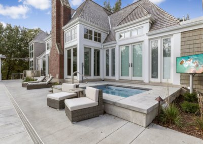 Remodeled backyard with hot tub, television and sliding door.