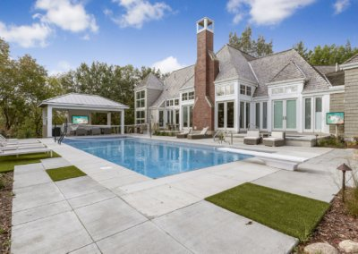 Rear exterior with in ground pool, covered patio, hot tub and turf.