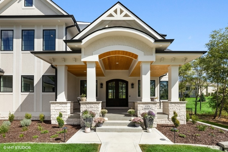 Front porch with stone columns, rounded arches and interesting roofline